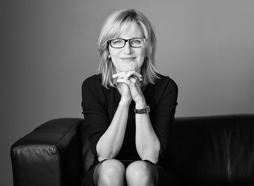 Petra van Laak fotografiert von Karoline Wolf sitzend auf Sofa