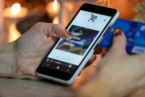 Bild von Hand mit Handy und Kredtkarte für SSL verschluesselten Online-Einkauf